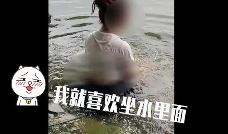 湖南女子不听工作人员劝告,执意坐在湖中,还指责工作人员